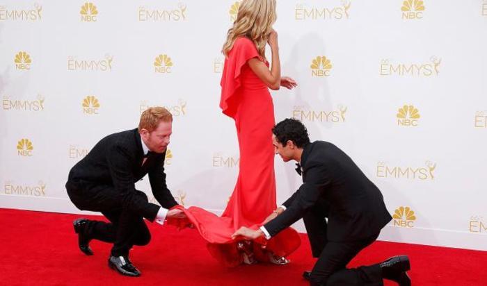 Актер Джесси Тайлер Фергюсон и модельер Зак Позен поправляют платье Хайди Клум перед 66 церемонией Primetime Emmys в Лос-Анджелесе.