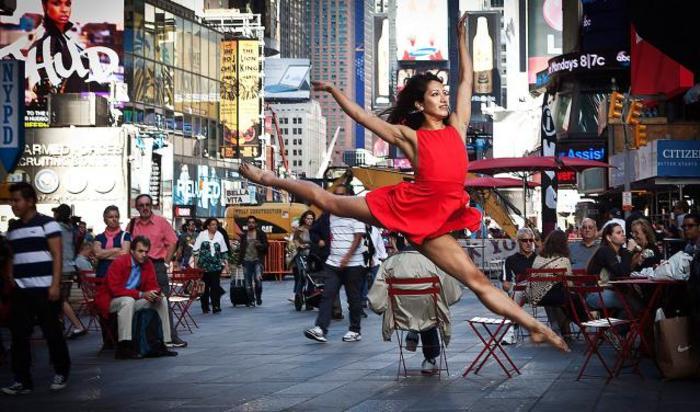 Танцовщица позирует фотографу в рамках проекта «Танец как искусство» на Таймс-сквер в Нью-Йорке, США.