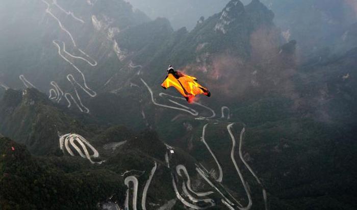 Парашютист в вингсьюте в Национальном парке Tianmen Mountain в Чжанцзяцзе в провинции Хунань, Китай.