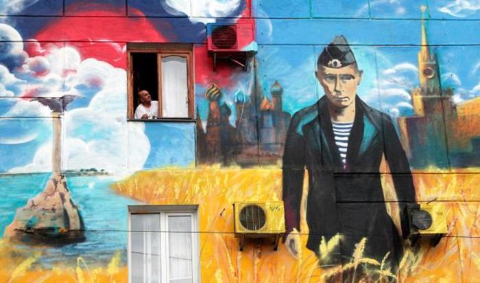 Граффити с изображением Кремля, президента России Владимира Путина и российским флагом на стене жилого дома в Севастополе.