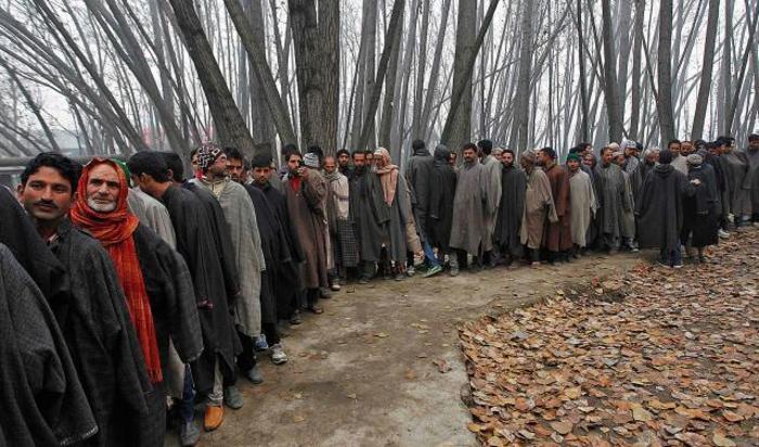 Люди стоят в очереди на голосование во время выборов в законодательное собрание Джамму и Кашмира, Индия.