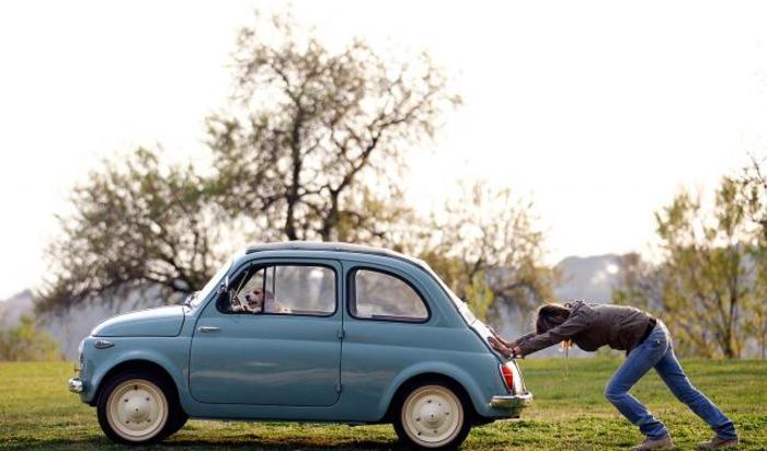 Женщина толкает свой автомобиль с собакой на водительском месте в районе Рима, Италия.