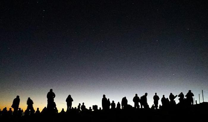 Люди встречают рассвет на вершине вулкана Халеакала на о. Мауи.