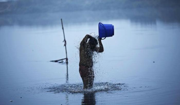 Мужчина купается в реке Ямуна ранним зимним утром в Нью-Дели, Индия 21 декабря 2014