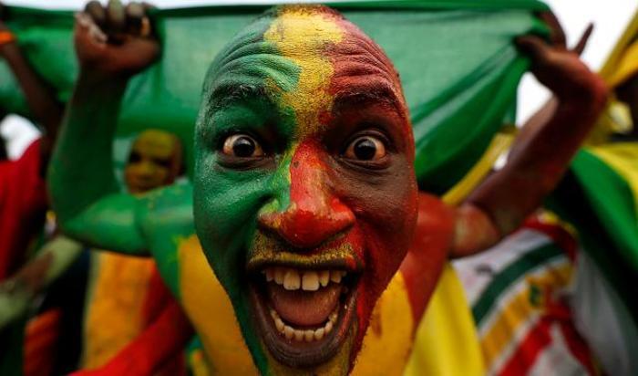 Болельщик сборной Мали, раскрашенный в цвета национального флага, во время прибытия команды на матч в рамках Кубка африканских наций 2015 в Монгомо, Экваториальная Гвинея.