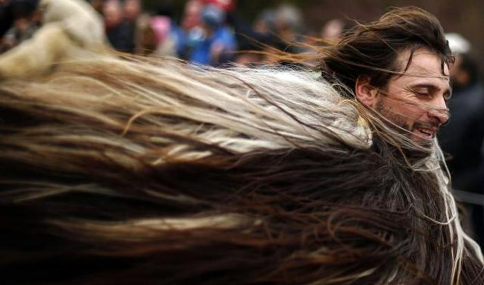 Человек в костюме из меха животного во время Международного Фестиваля маскарадных игр в городе Перник, Болгария 31 января 2015.