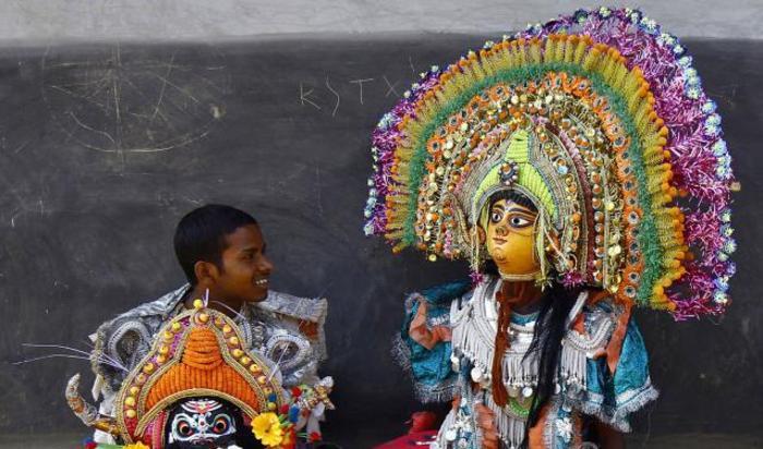 Танцоры в масках отдыхают во время фестиваля Чхау в деревне Мальти в Пурулия, Индия.