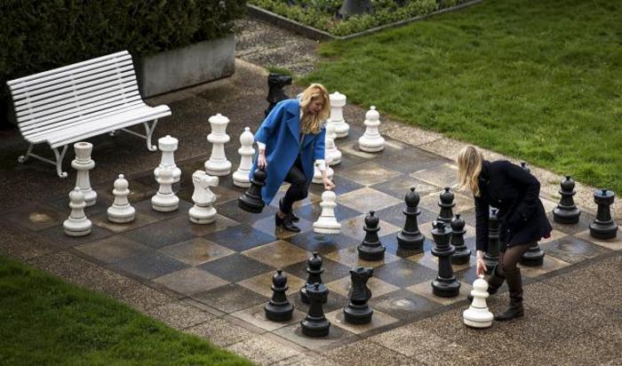 Российские журналисты играют в гигантские шахматы во дворе отеля Beau Rivage Palace в Лозанне, Швейцария 1 апреля 2015.