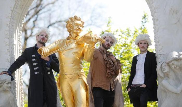 Участники группы Johann Sebastian Bass позируют рядом с памятником Иоганну Штраусу в Вене, Австрия