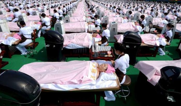 Группа из 1000 женщин получают массаж лица одновременно на спортивном стадионе в Цзинань, провинции Шаньдун, Китай 4 мая 2015.