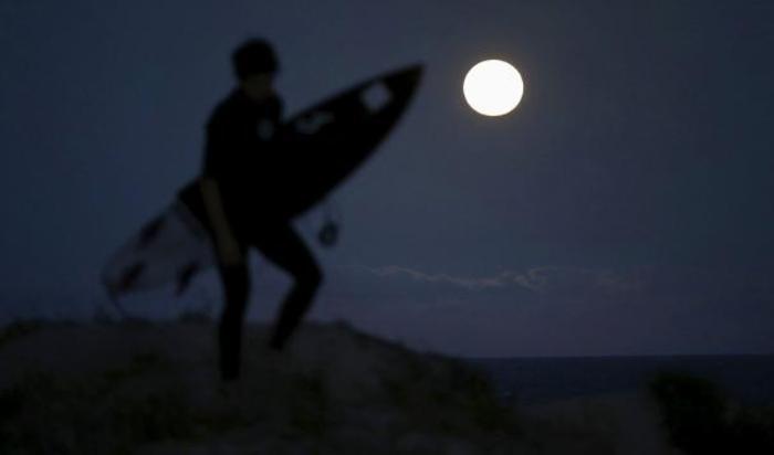 Полная луна видна над побережьем в Сиднее, Австралия 4 мая 2015.