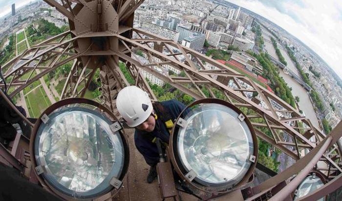 Рабочий меняет лампу на Эйфелевой башне в Париже.