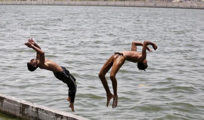 Мальчики прыгают в воды реки Sabarmati в Ахмедабаде, Индия 24 мая 2015.