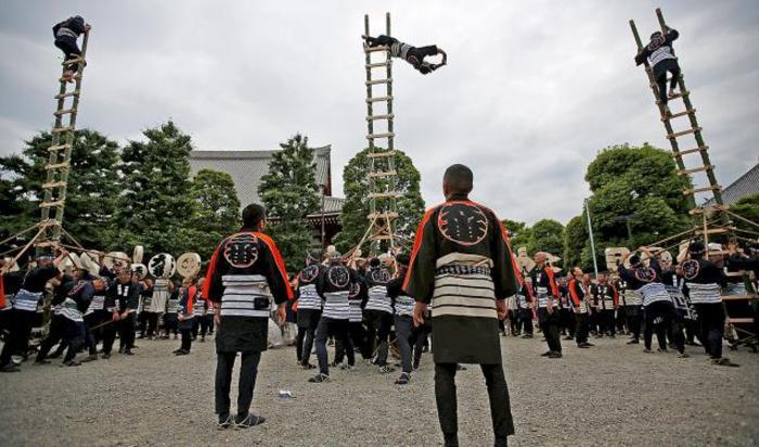 Люди в костюмах пожарных выполняют акробатические трюки на бамбуковых лестницах во время поминальной церемонии по пожарникам, погибшим при выполнении своих обязанностей за последние 300 лет. Токио, Япония.