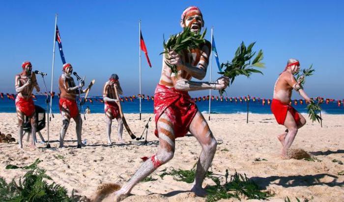 Люди, одетые в традиционные костюмы, исполняют танец аборигенов на пляже Куги Сидней, Австралия 27 мая 2015.