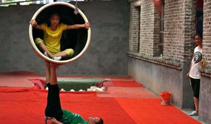 Студенты акробатической школы тренируются в селе Sanwang, провинция Аньхой, Китай.