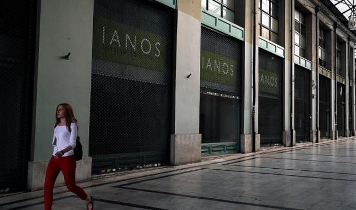 Женщина идет по опустевшему торговому центру в Афинах, Греция, 2 июля 2015.