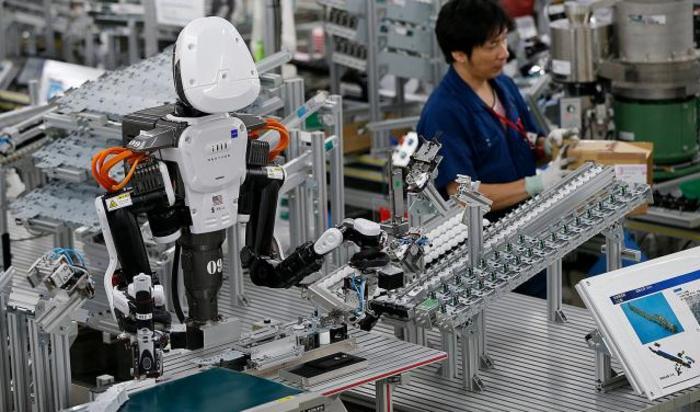 Робот-гуманоид работает вместе с людьми на фабрике в Казо, Япония.