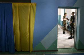 Украинские солдаты стоят около стенды во время голосования на президентских выборах в избирательном участке 25 мая 2014.